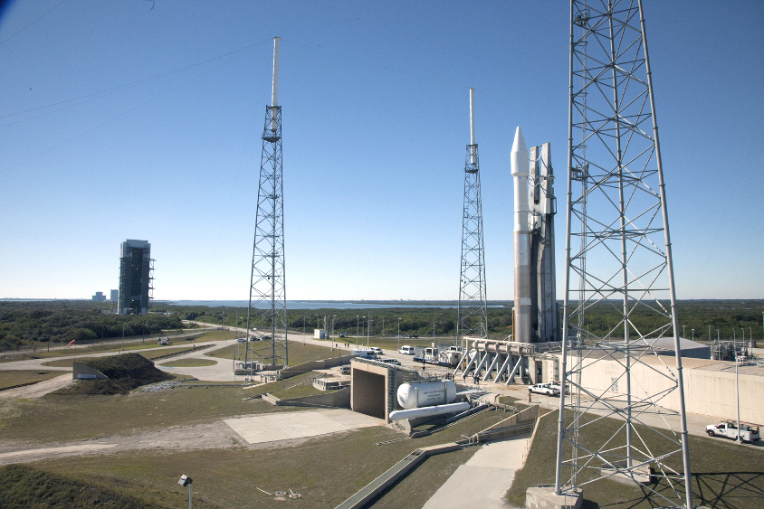 A silver rocket stands on the launch pad with tall grey lightning protection towers standing close by.